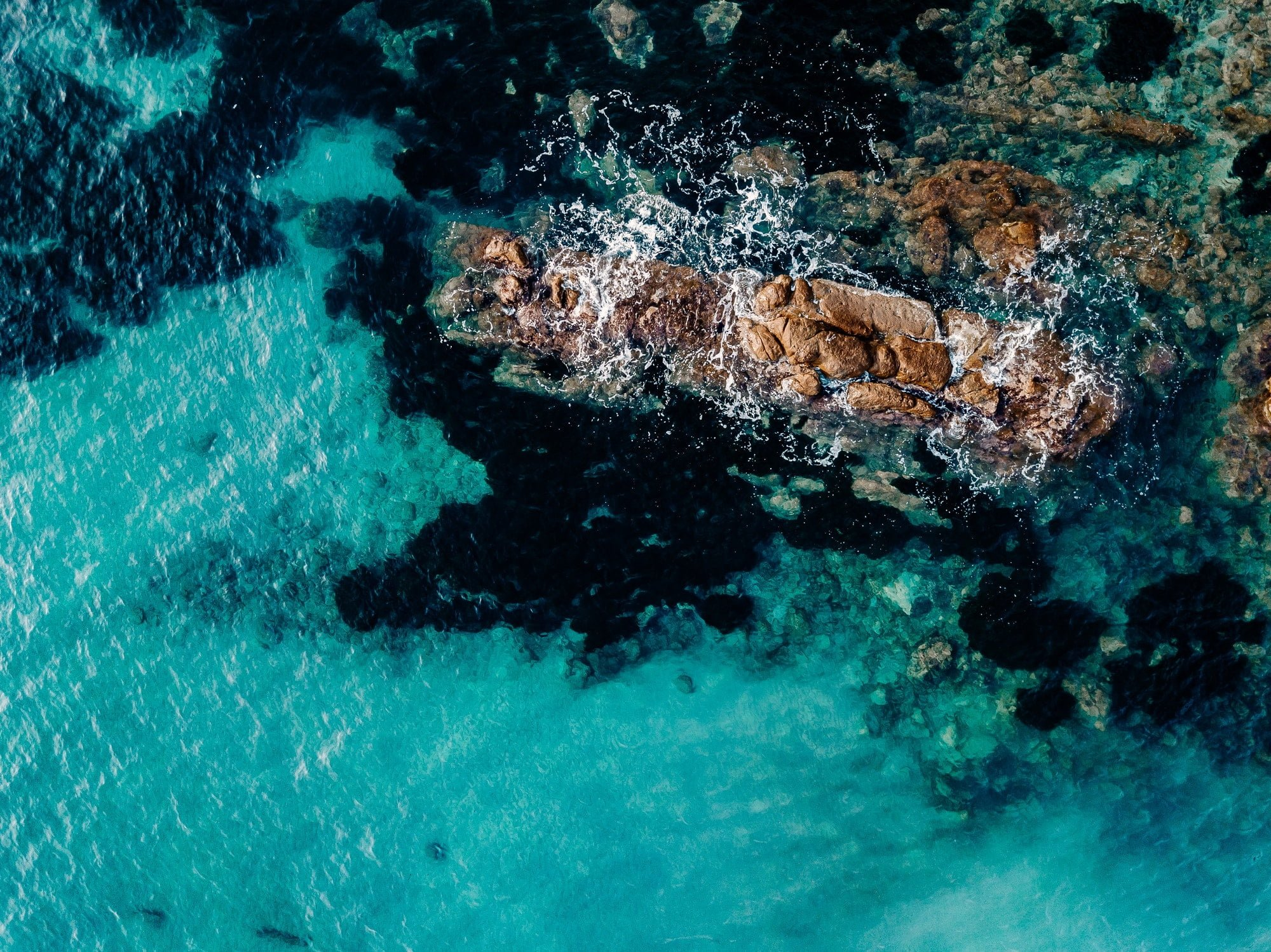 Aerial view of ocean waves and rocks. Blue sea surface