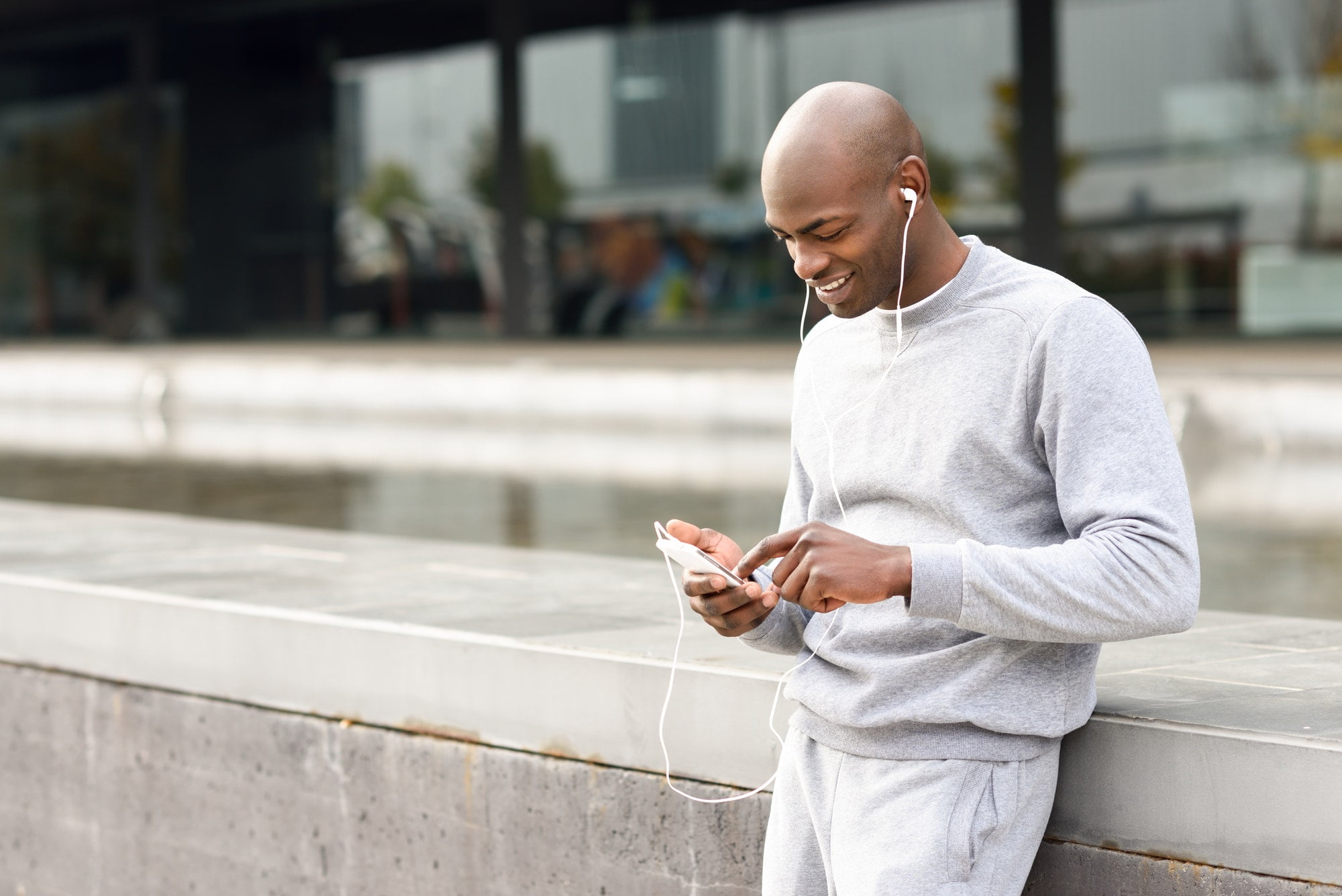 Attractive black man listening to music with headphones in urban