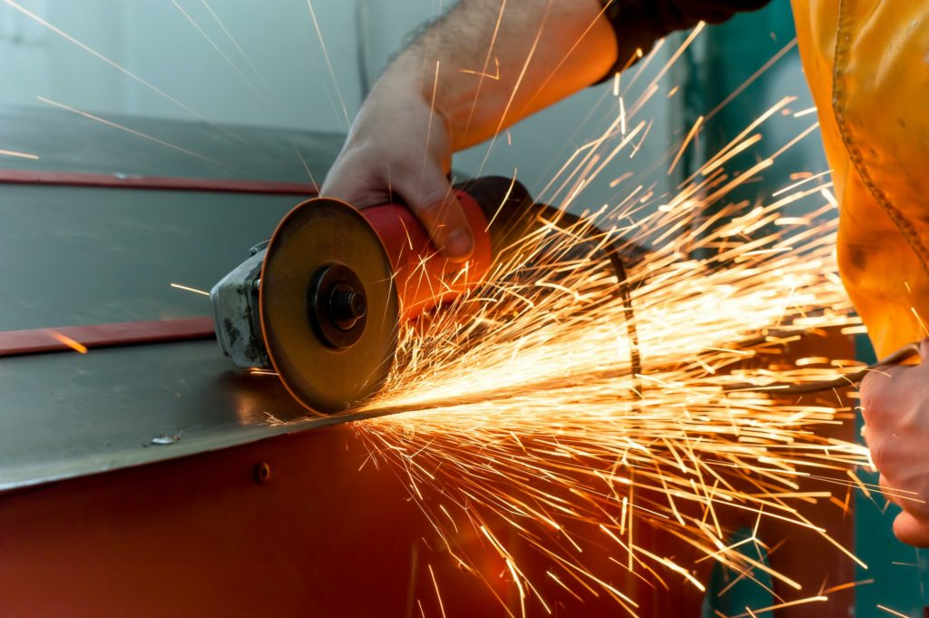 auto mechanic grinding metal on a metal surface