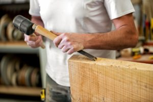 Carpenter or woodworker working with a chisel