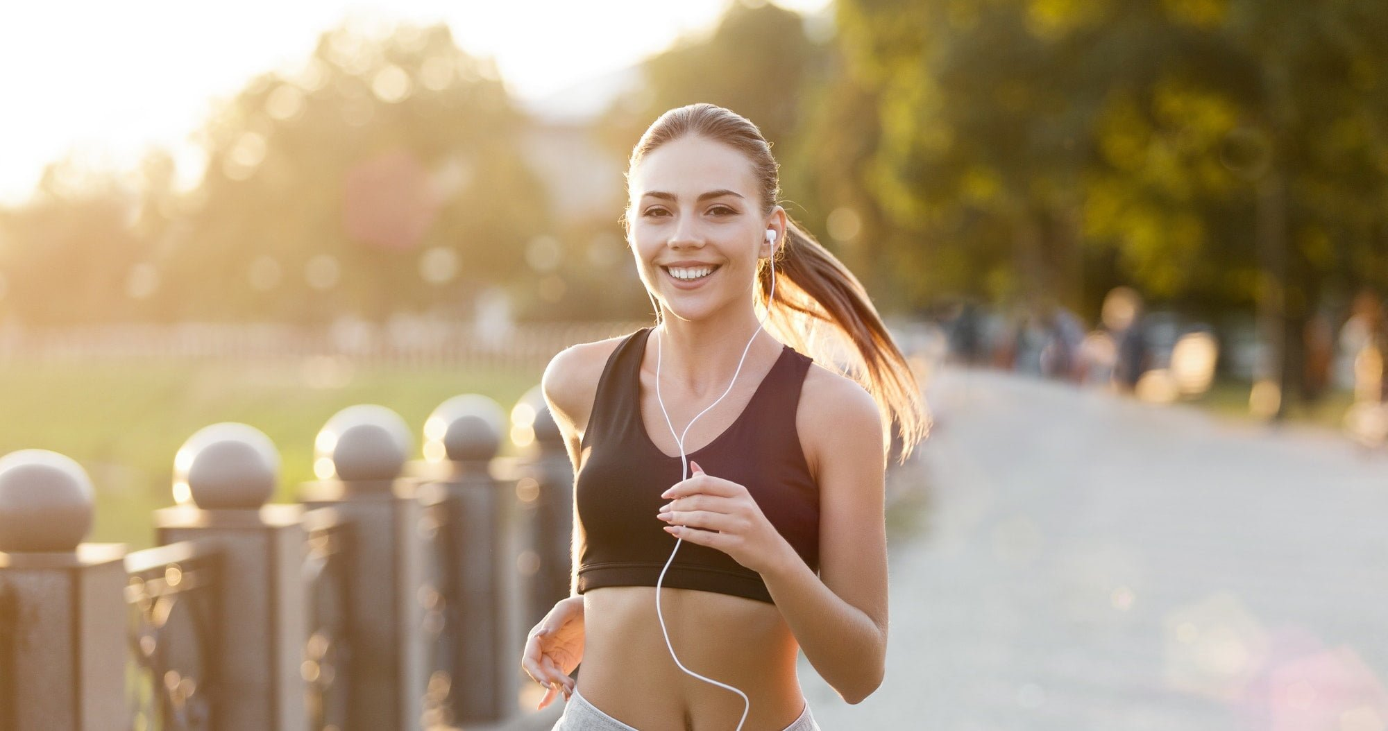 Cheerful woman with headphones running in park