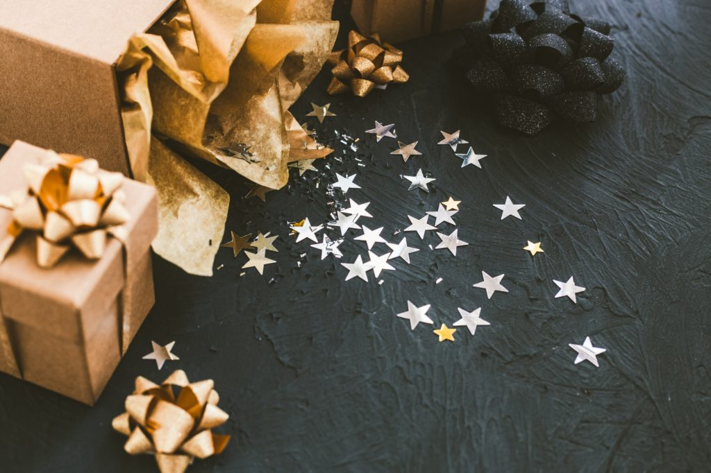 Christmas gifts on a black background. Open gift with stars.