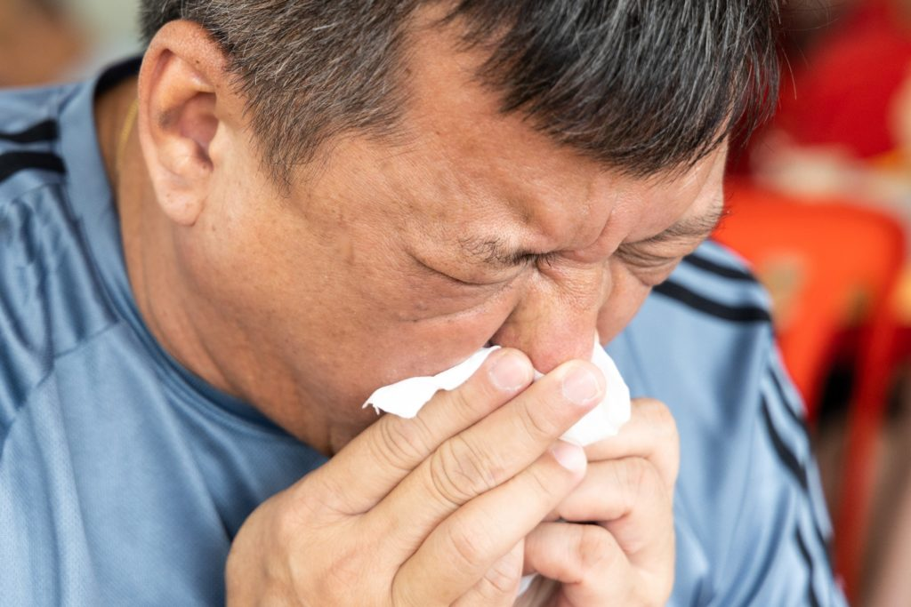 Close-up of Asian man sneezing onto tissue paper, covering mouth and nose.