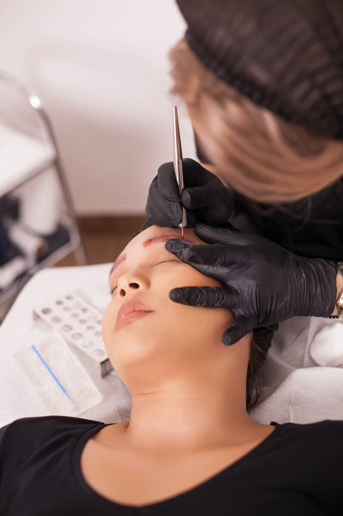 Female beautician using modern technology for tattoo removal