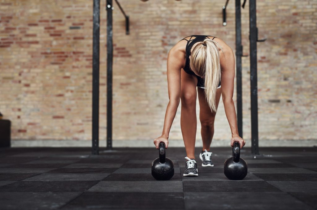Fit young woman weight training alone in a gym