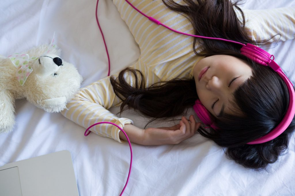 Girl listening to music while sleeping on bed