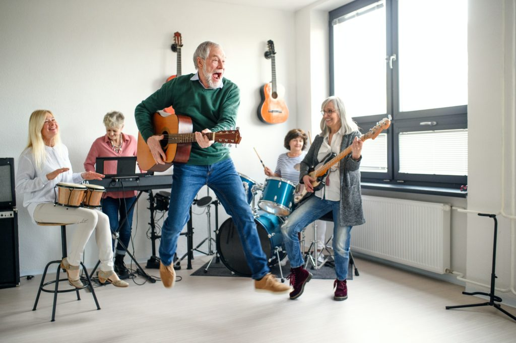 Group of senior people playing musical instruments indoors in band