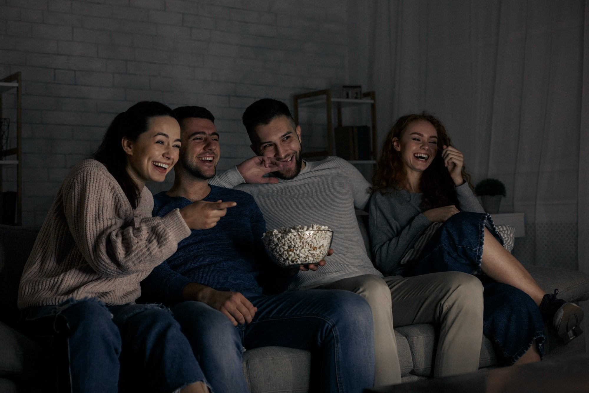 Happy friends watching comedy film at home
