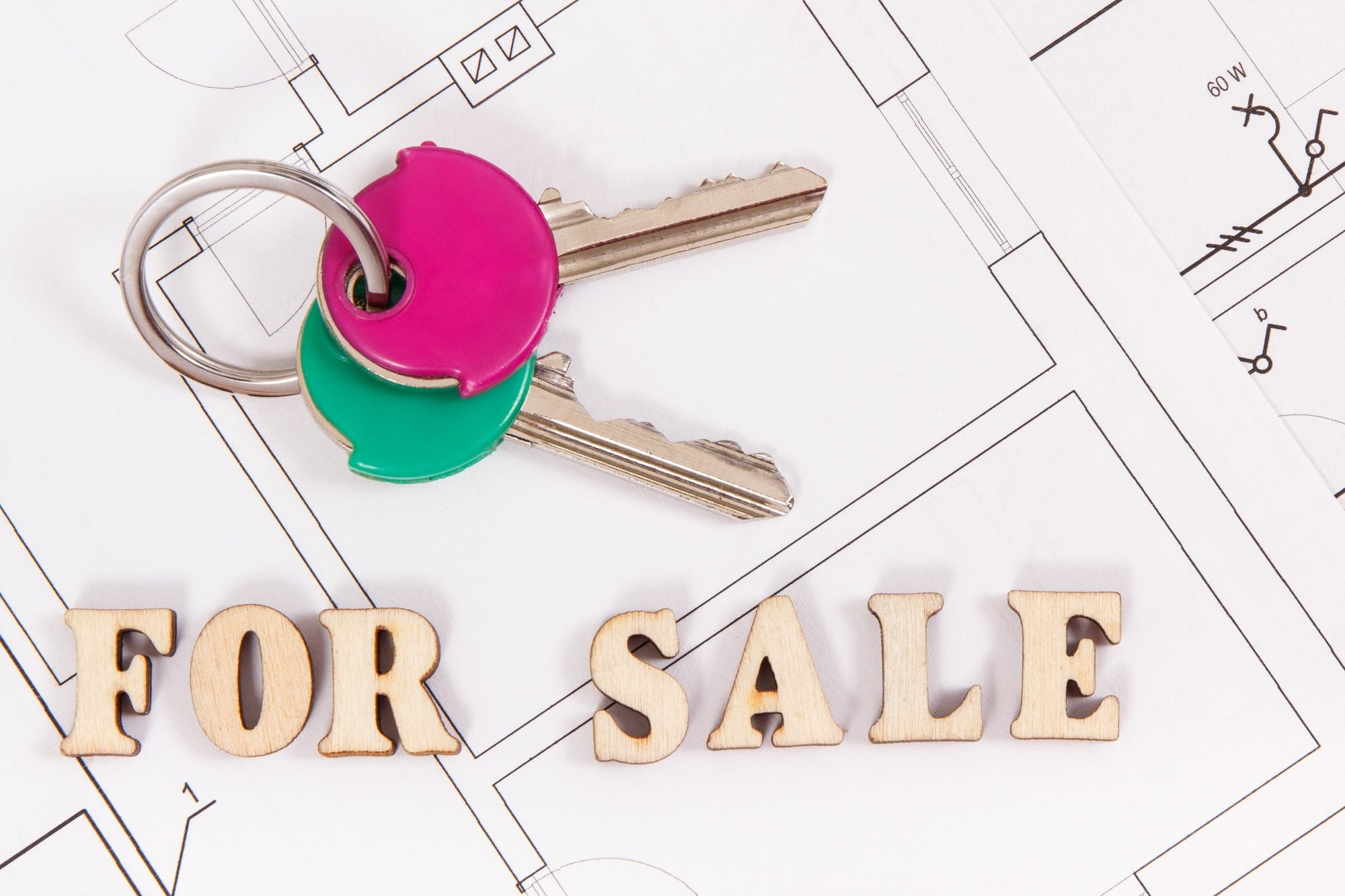 Home keys with inscription for sale on housing plan, concept of selling or buying house