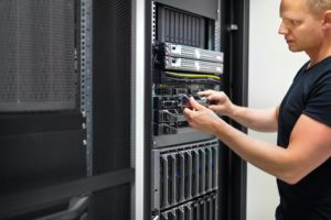 IT Consultant Monitors Servers In Data Center