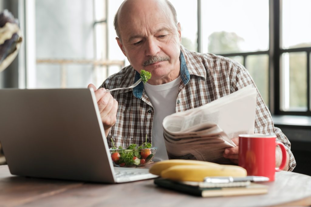 Man having healthy breakfast while sitting at the kitchen table with laptop