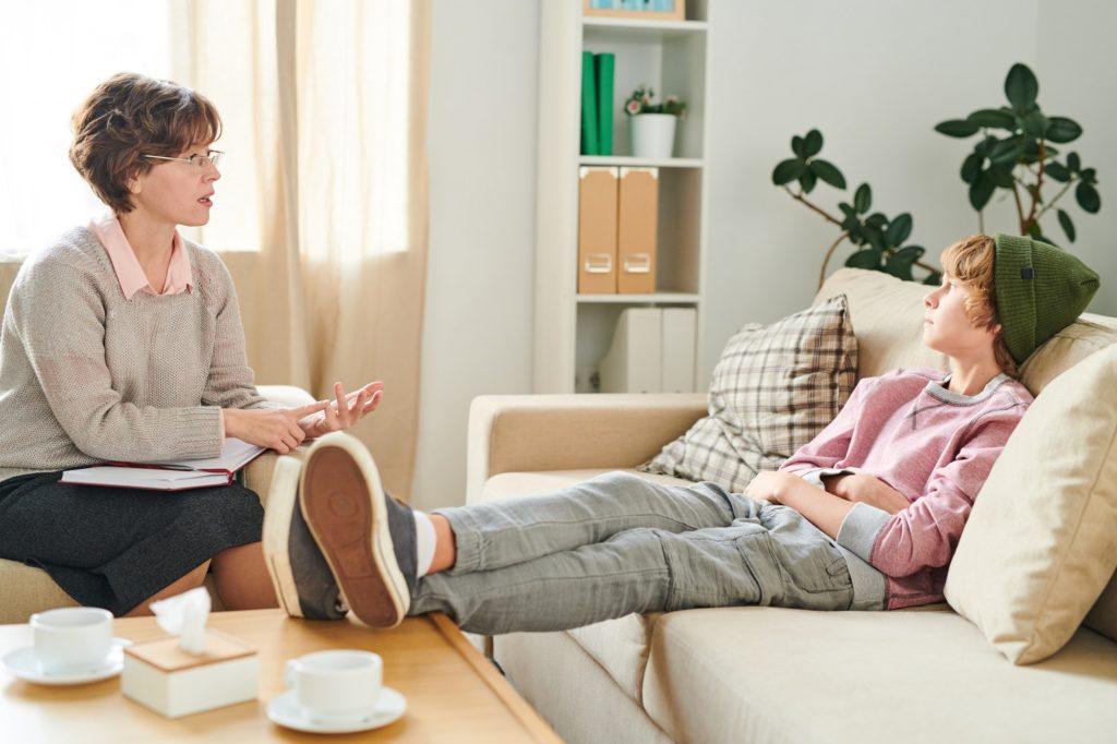 Mature psychiatrist talking to teenager ignoring her