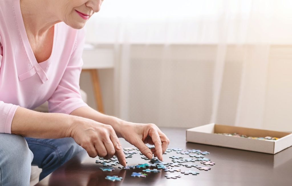 Senior woman playing jigsaw puzzle on wooden table at home