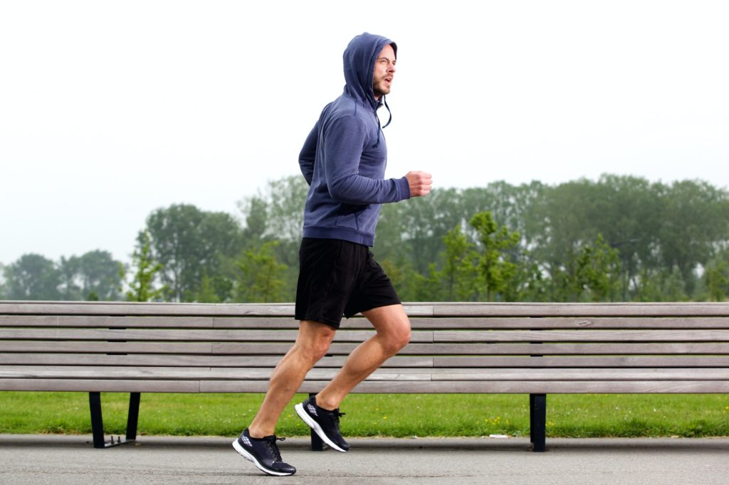 Sporty older man running in park