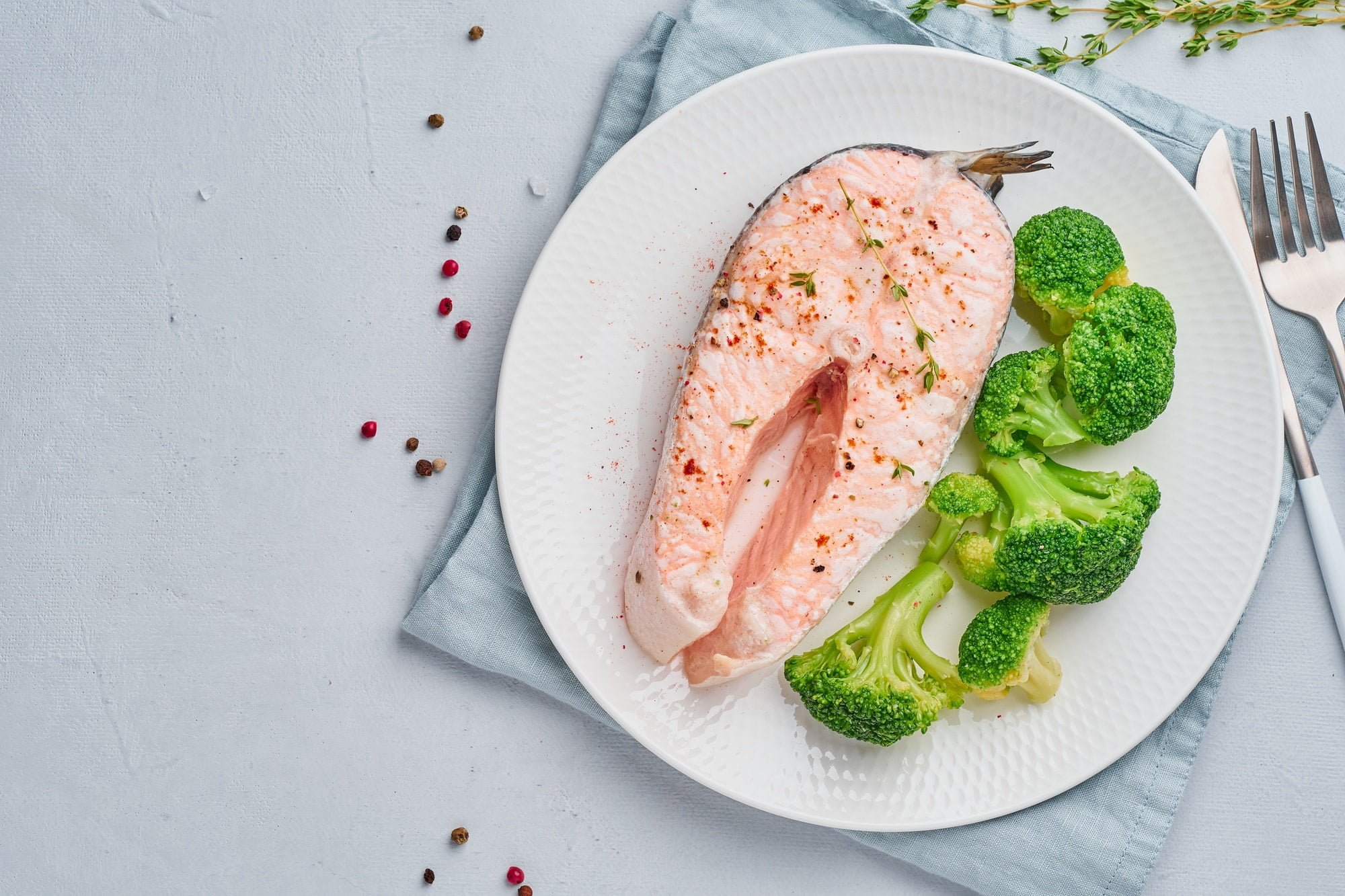 Steam salmon, broccoli, paleo, keto or fodmap diet. White plate on blue table, top view