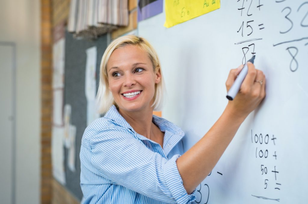 Teacher teaching math on whiteboard