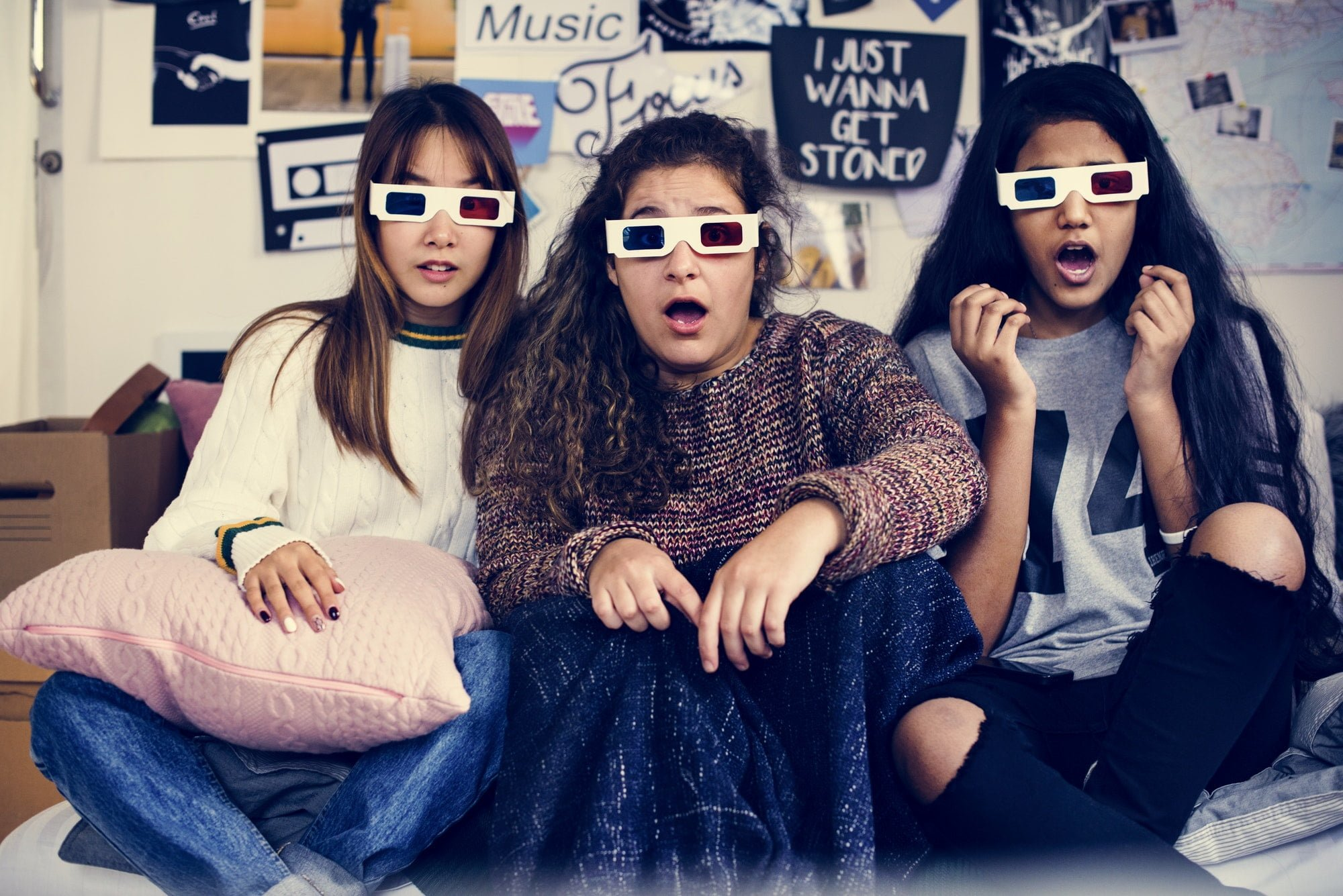 Teenage girls wearing 3d movie eyeglasses surprised scared and watching TV