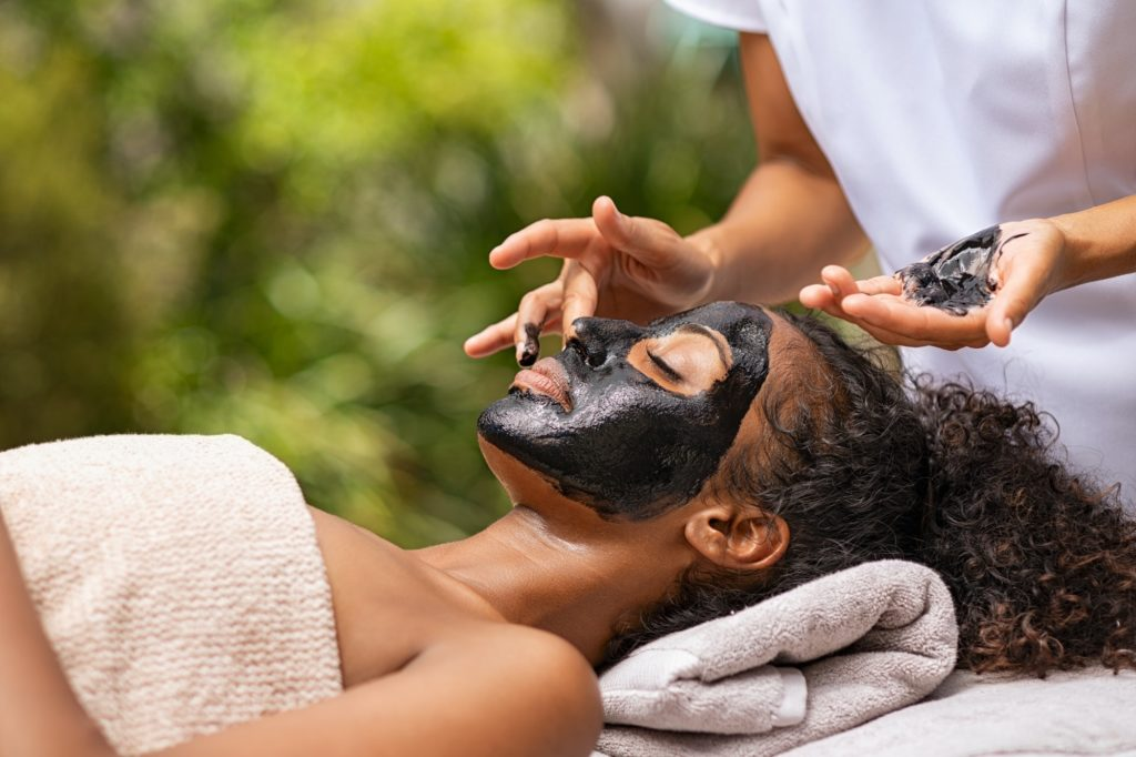 Woman getting charcoal facial at beauty resort