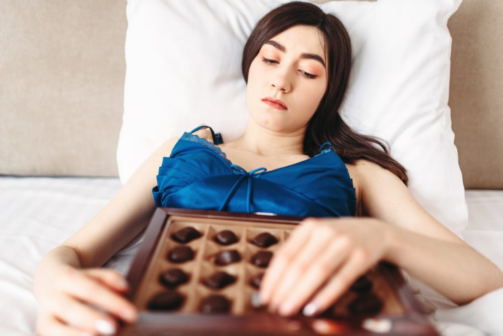 Woman lies in bed and eats sweets, depression