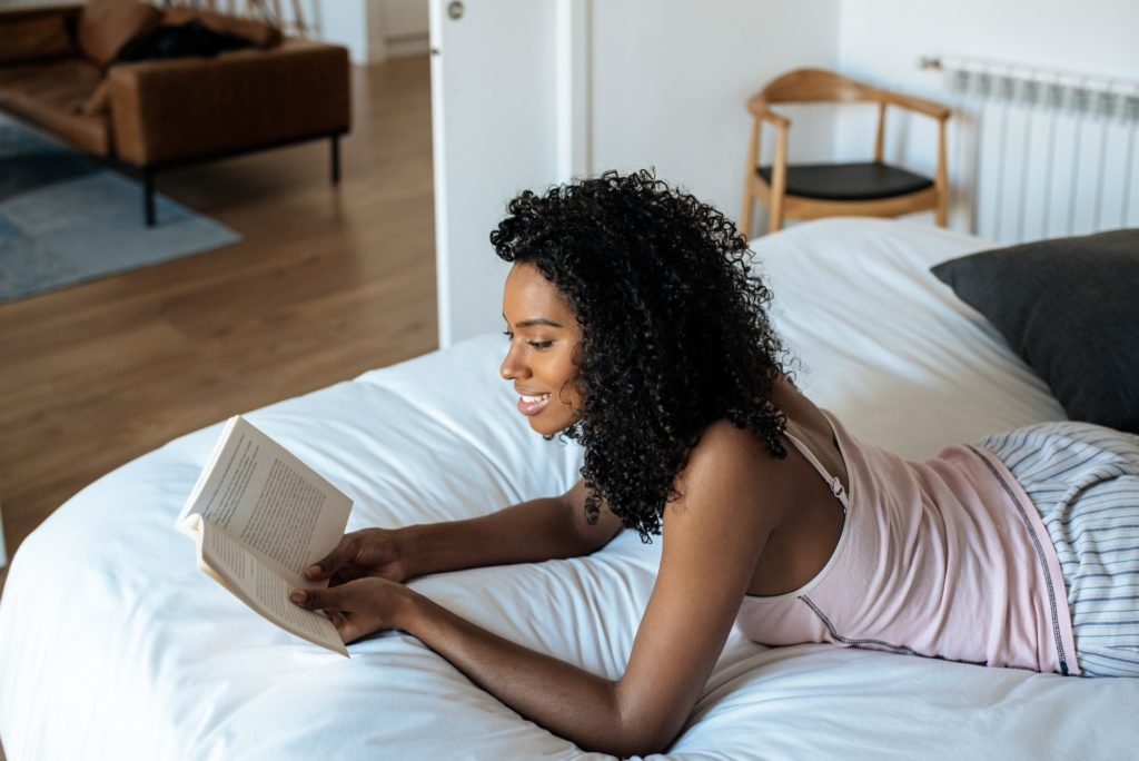 Woman lying down on bed reading a book