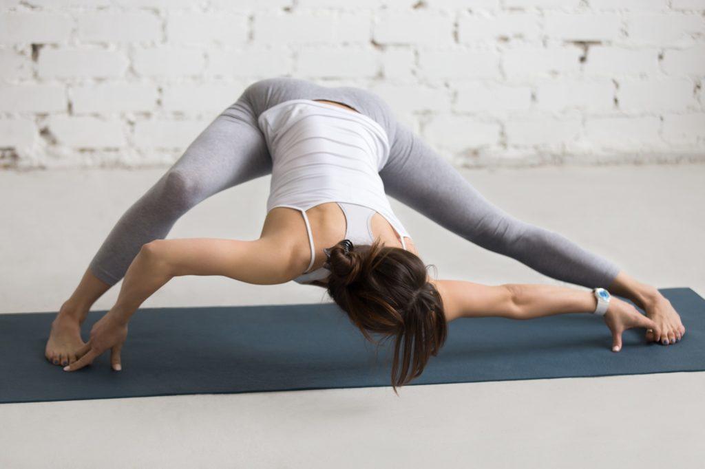 Yogi female doing stretching pilates exercise