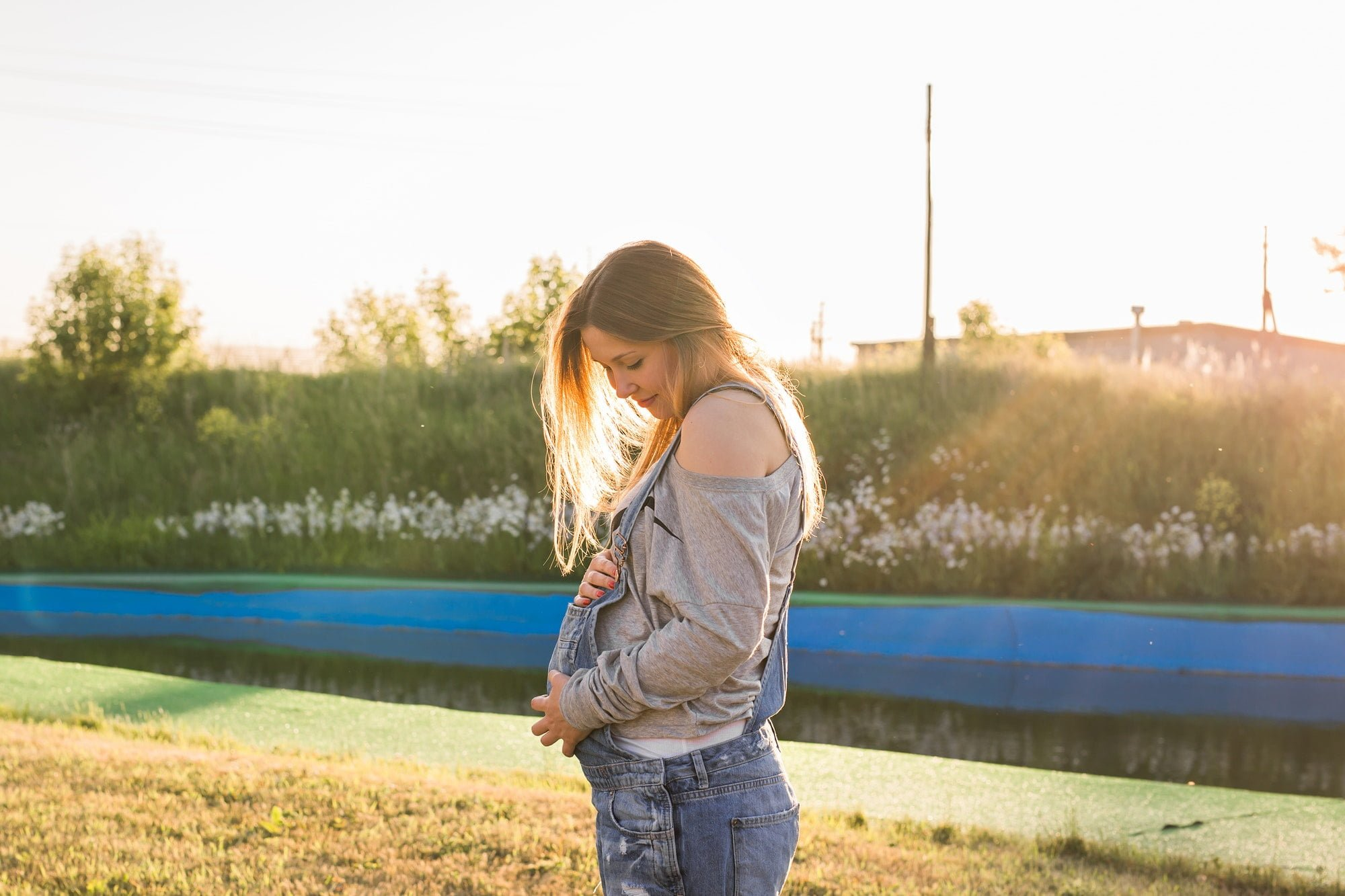 young happy pregnant woman relaxing and enjoying life in autumn nature