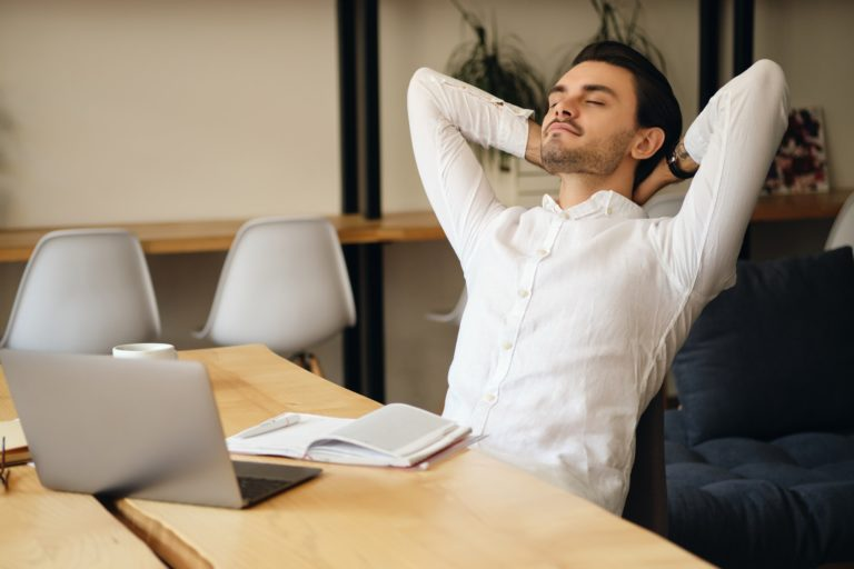 Young man sitting at the table with laptop and notepad leaning on chair dreamily resting in office
