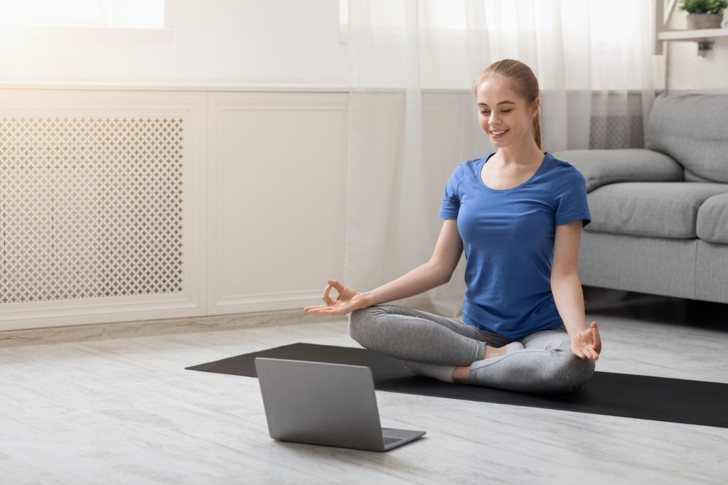 Young spiritual woman practicing yoga at home with laptop