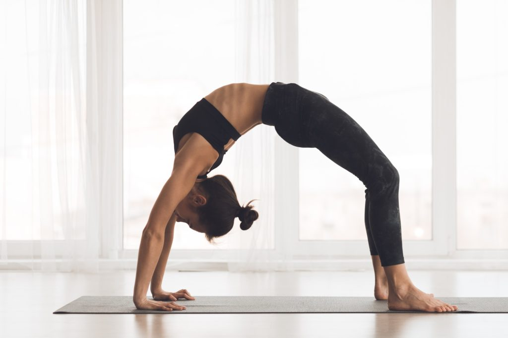 Young woman doing yoga exercise in Bridge Pose