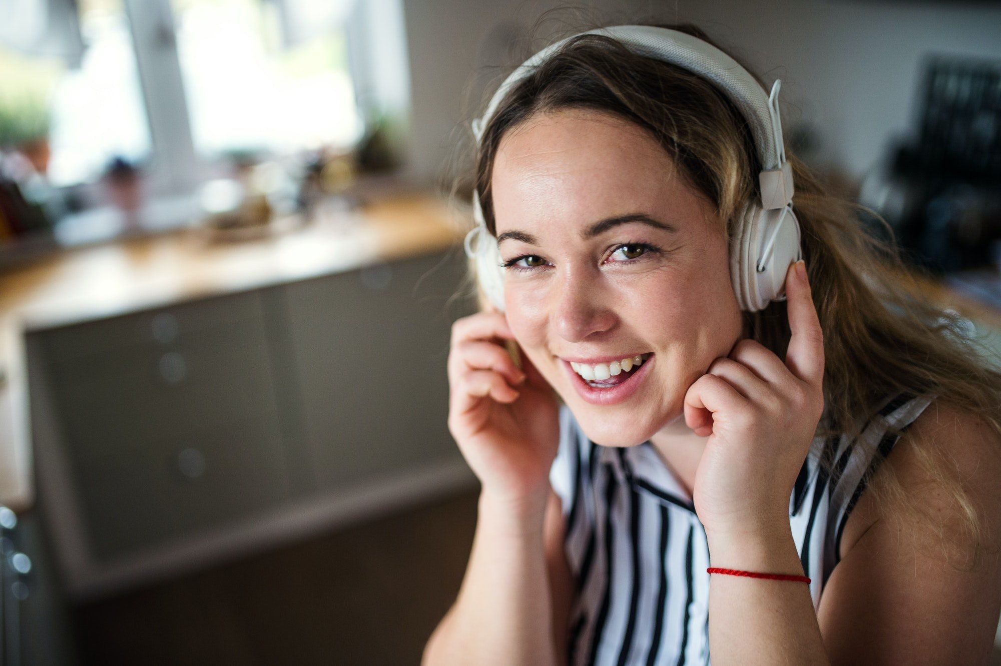 Young woman with headphones relaxing indoors at home, listening to music