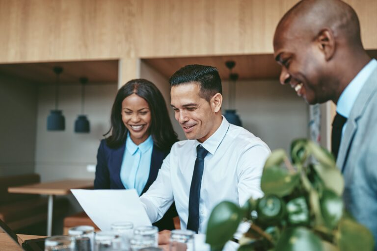 Three diverse businesspeople laughing while going over documents together