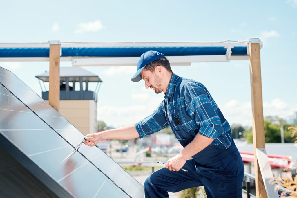 Young technician master in workwear bending over solar panel on the roof