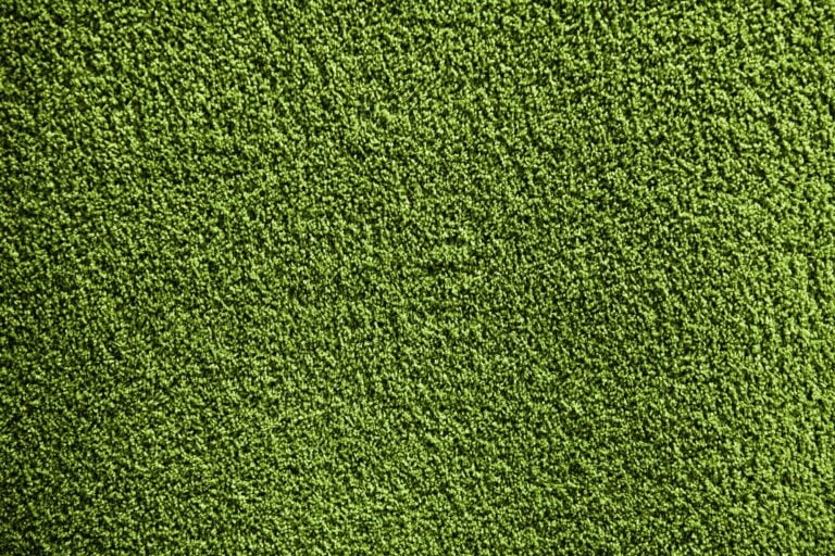 Artificial green carpet texture close-up background