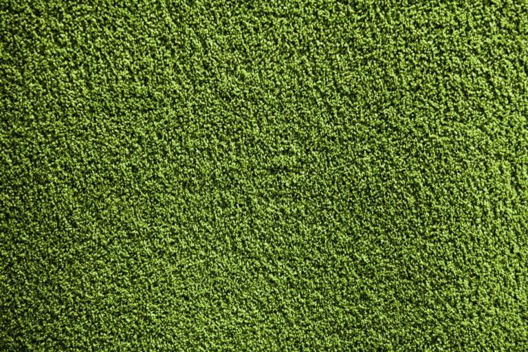 Artificial green carpet texture close-up background