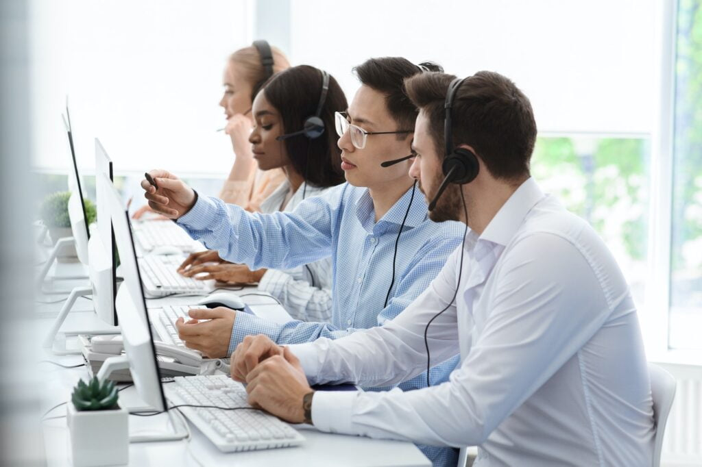 Customer support service. Hotline operator helping his colleague at call centre office