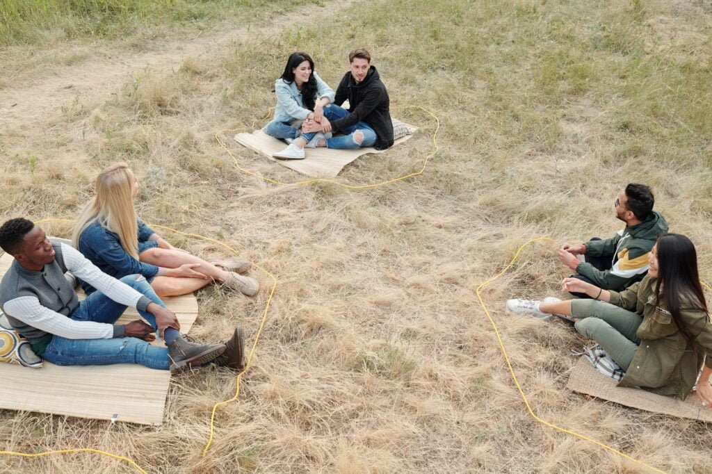 Three intercultural couples keeping social distance while sitting on dry grass