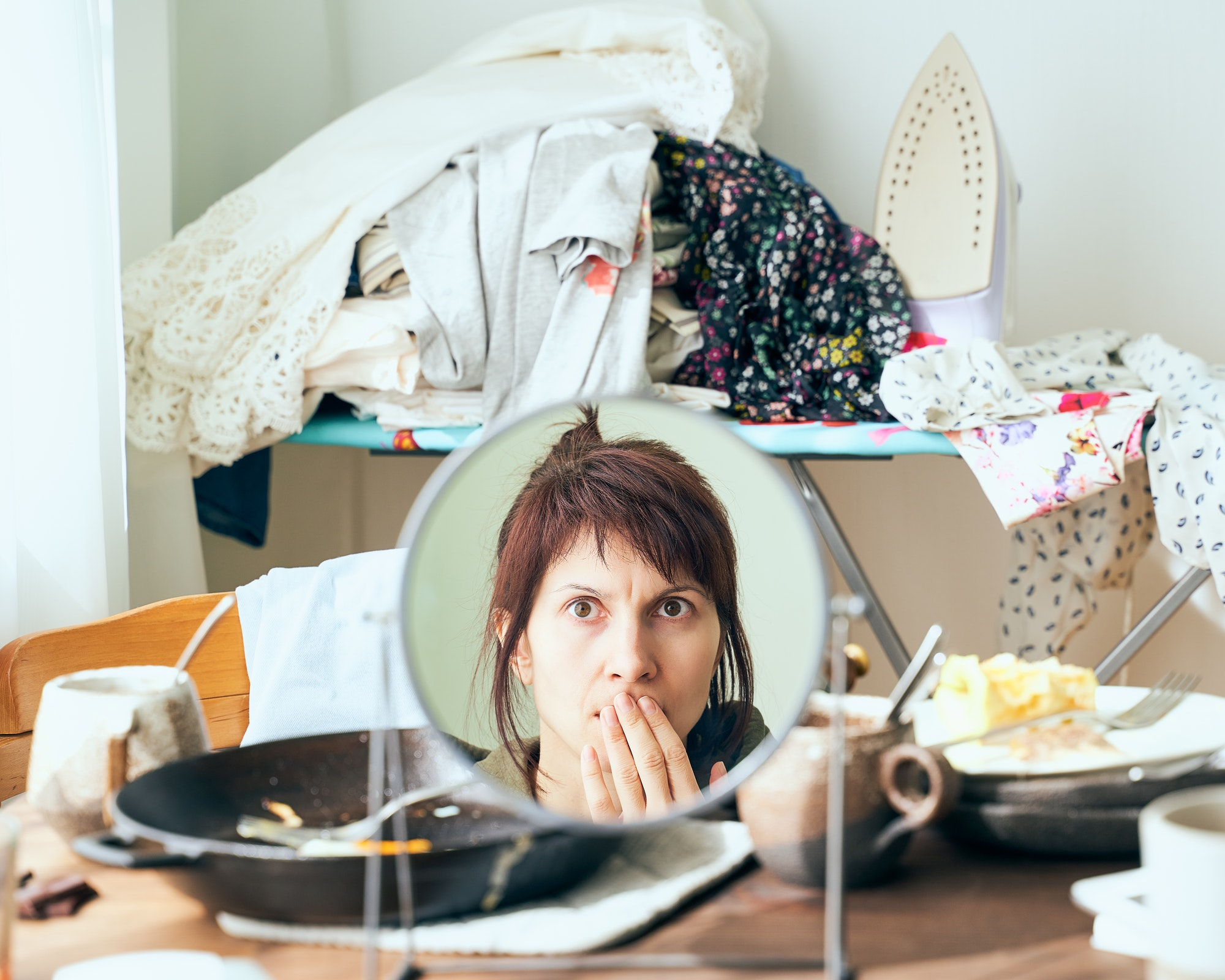 Woman looks with horror and fright at herself in mirror against background of mess