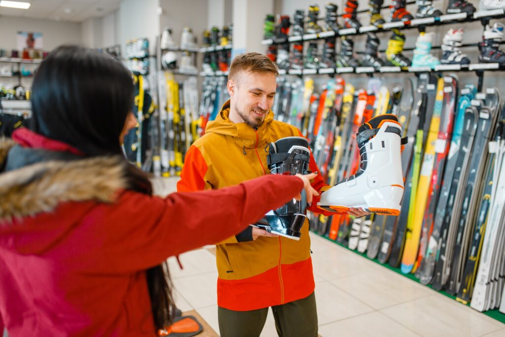 Couple choosing ski or snowboarding boots