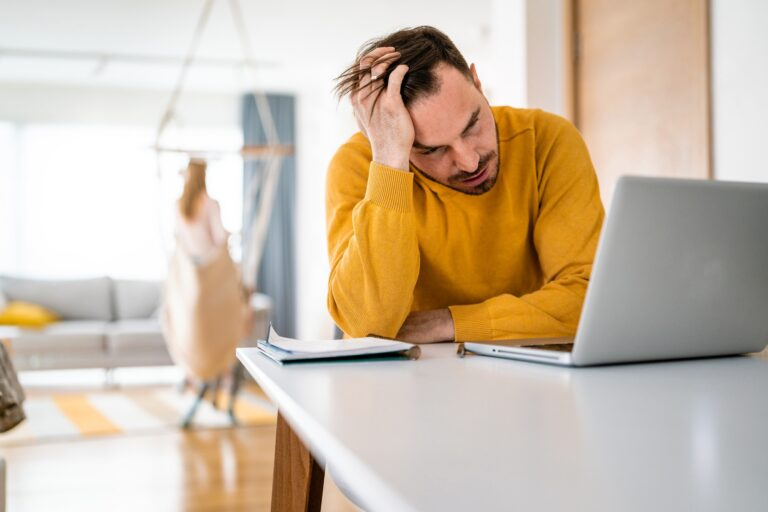 Frustrated young man working on laptop at home