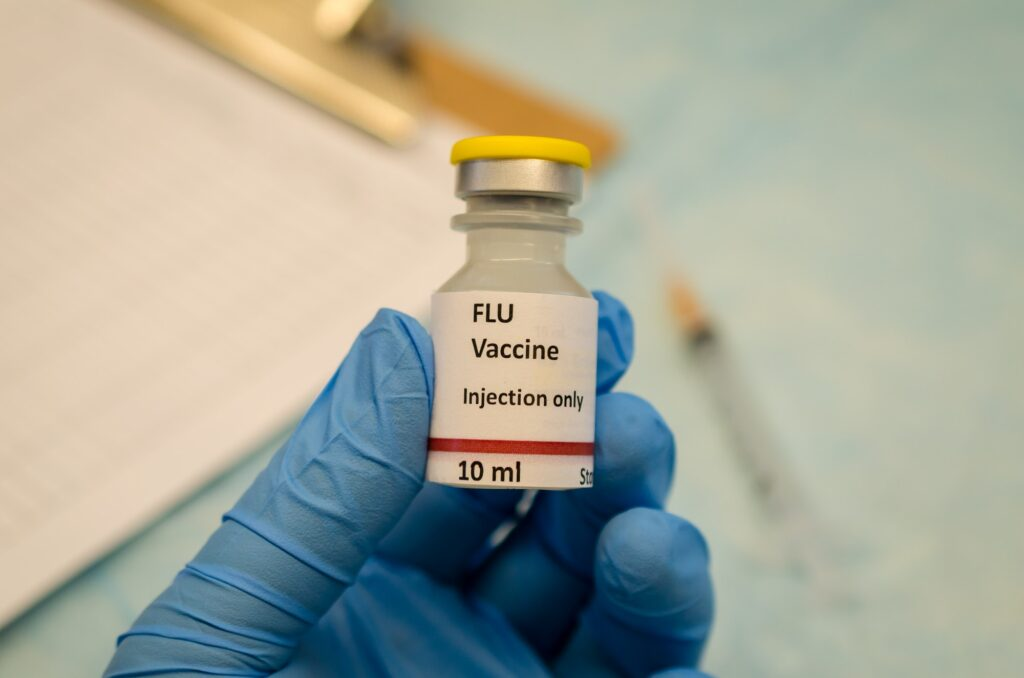 Flu control by flu vaccine holding in hand. Flu vaccine is one key way to help keep the elderly healthy during flu season.