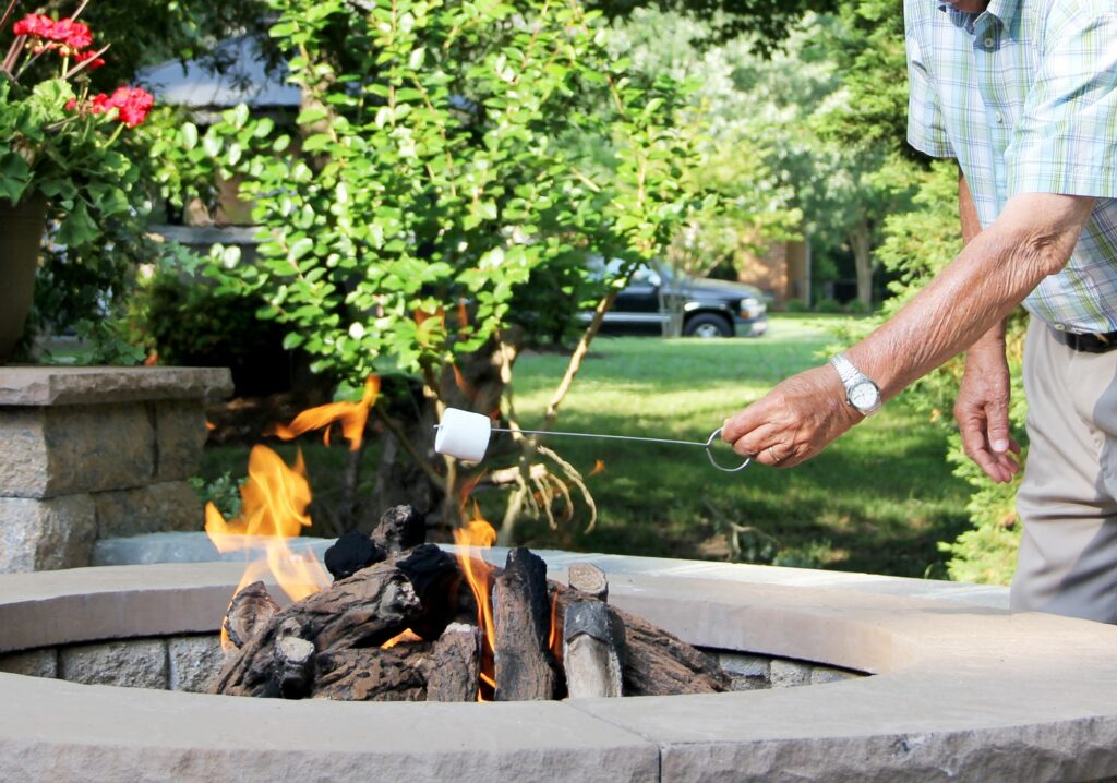 Elderly man in the backyard enjoying the fire pit and marshmallows during an outdoor gathering.