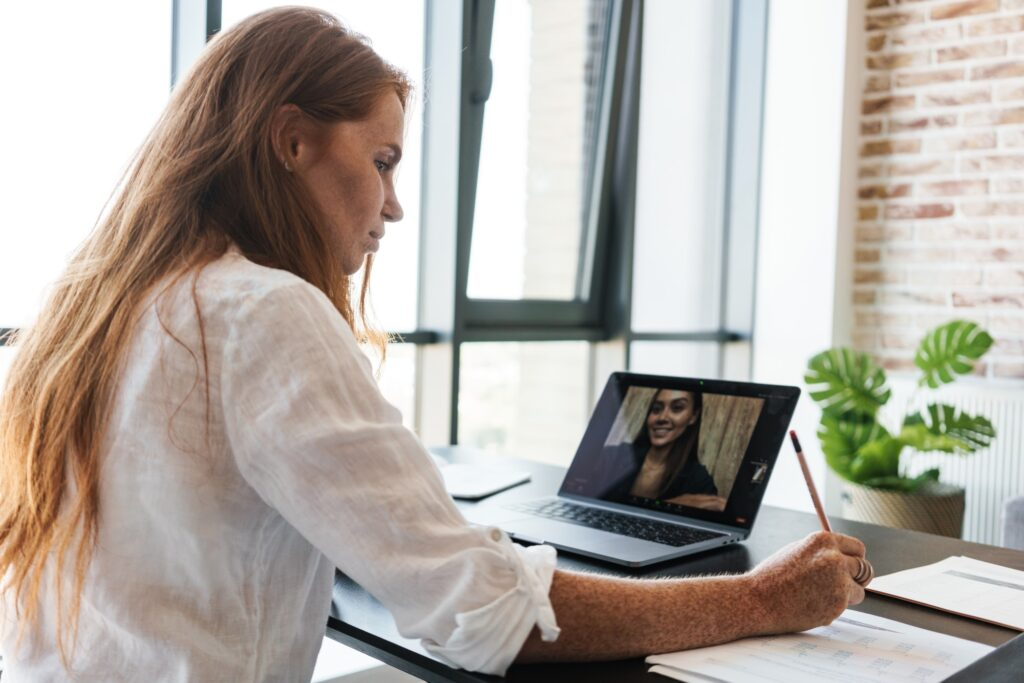 Image of businesswoman making call on laptop while sitting at table